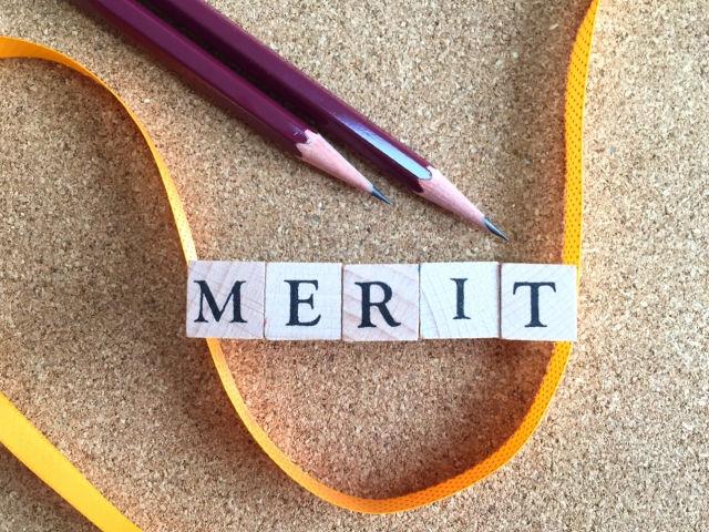 メリットと書かれた積み木と鉛筆